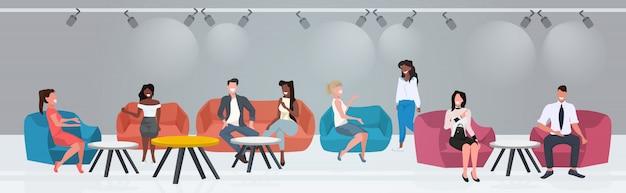 Persone di affari che si siedono ai tavoli del caffè che discutono durante la riunione moderna nel ristorante