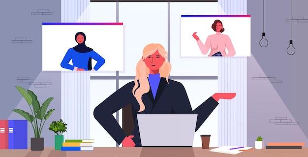 Imprenditrice avendo videochiamata di gruppo con colleghi di sesso femminile in browser web finestre di affari donne di affari che discutono durante la conferenza in linea illustrazione di vettore del ritratto orizzontale interno dell'ufficio