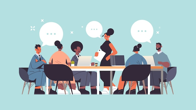 Leader della donna di affari che discute con il gruppo degli imprenditori della corsa della miscela durante la riunione di conferenza alla figura intera di lunghezza intera di concetto di comunicazione della bolla di chat della tavola rotonda