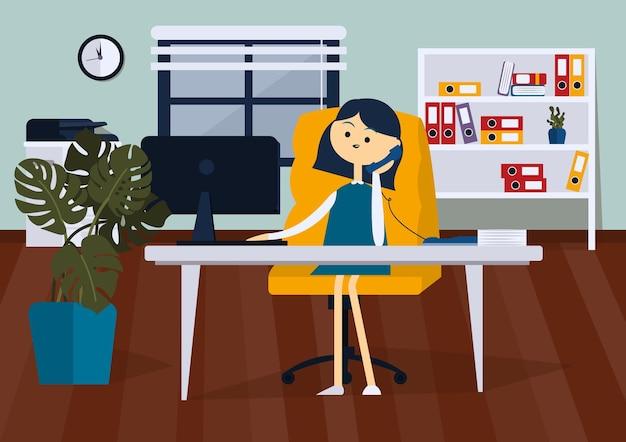 Donna d'affari seduta su una sedia da ufficio alla scrivania del computer sta parlando al telefono