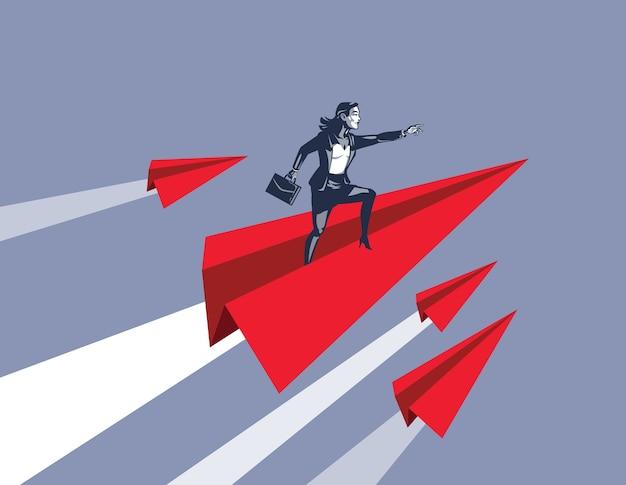 Imprenditrice in piedi sul razzo aeroplano di carta come simbolo di fiducia per affrontare il successo e il futuro d'oro