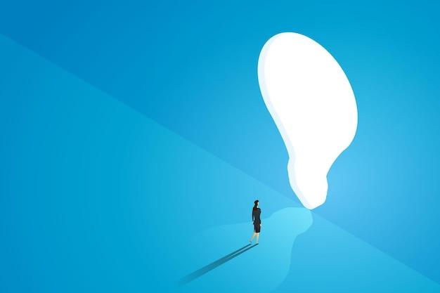 La donna d'affari sta di fronte a una grande porta con una lampadina luminosa