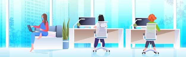 Donne d'affari in maschere che lavorano e parlano insieme nel centro di coworking coronavirus pandemia lavoro di squadra concetto moderno ufficio interno orizzontale