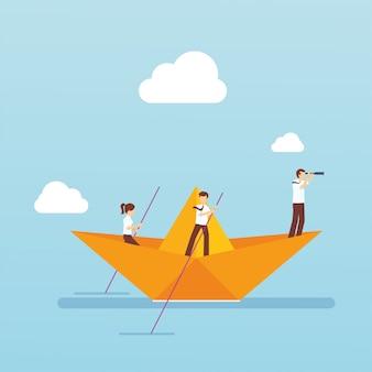 Squadra di affari con la barca di carta nell'oceano