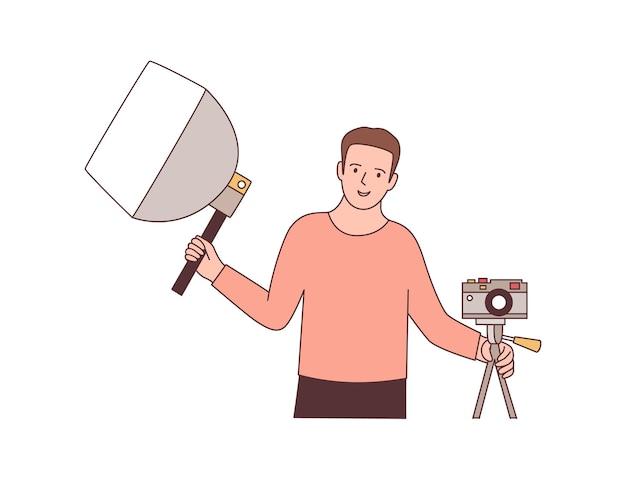 Cameraman con attrezzatura fotografica piatta illustrazione vettoriale. fotografo professionista che tiene softbox e fotocamera mirrorless. personaggio dei cartoni animati del lavoratore dello studio fotografico. elemento di design per sessioni fotografiche.
