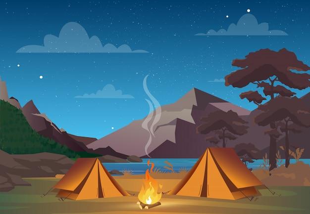 Campeggio notturno con splendida vista sulle montagne. serata familiare in campeggio. tenda, fuoco, foresta e sfondo di montagne rocciose, cielo notturno con nuvole.