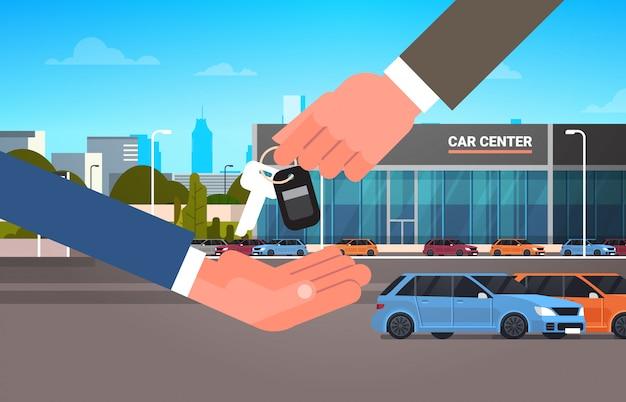Concetto di noleggio o di vendita di acquisto dell'automobile, mano dell'uomo del venditore che fornisce le chiavi al centro della sala d'esposizione del proprietario
