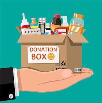 Scatola di cartone piena di farmaci in mano. oggetti necessari per la donazione. diverse bottiglie di pillole, sanità, farmacia.
