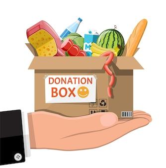 Scatola di cartone piena di cibo in mano. oggetti necessari per la donazione. acqua, pane, carne, latte, frutta e prodotti vegetali.