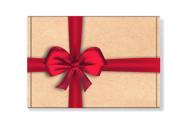 Confezione di cartone scatola con grande fiocco di nastro rosso isolato su sfondo bianco.