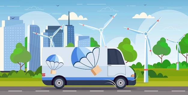 Furgone del carico che guida la scatola del pacchetto della strada con il paracadute che vola giù dal orizzontale moderno del fondo di paesaggio urbano dei generatori eolici di concetto di servizio di consegna espressa espressa