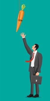 Carota su un bastone e uomo d'affari. metafora del concetto di motivazione, stimolo, incentivo e raggiungimento dell'obiettivo. bastone da pesca in legno con carota appesa