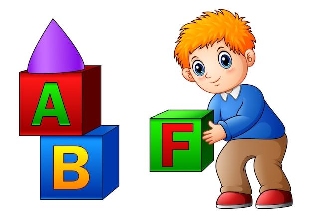 Ragazzo di cartone animato che gioca con i cubi di alfabeto