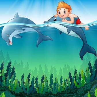Ragazzo di cartone animato con i delfini nel mare