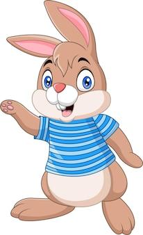 Coniglietto del fumetto che indossa vestiti blu sventolando