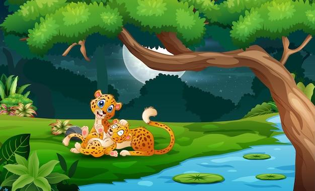 Ghepardo cartone animato con cuccioli in riva al fiume di notte