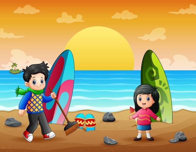 Bambini del fumetto che puliscono rifiuti sulla spiaggia Vettore Premium