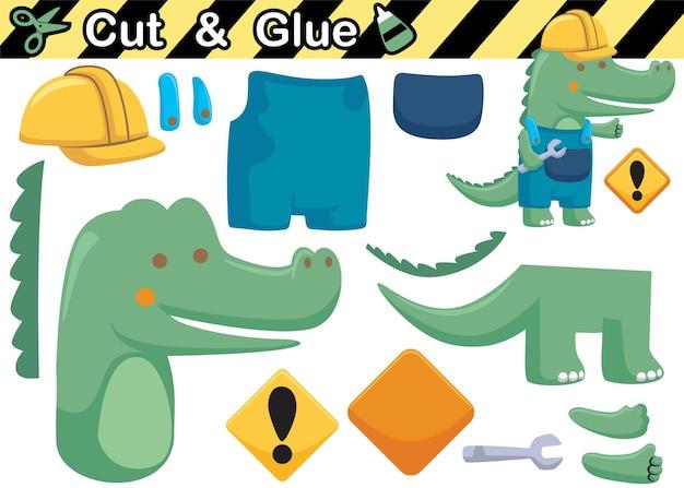 Cartone animato di coccodrillo che indossa l'uniforme del lavoratore mentre si tiene la chiave inglese. gioco di carta educativo per bambini. ritaglio e incollaggio