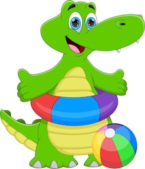 Coccodrillo simpatico cartone animato con la palla gonfiabile e l'anello di nuoto gonfiabile
