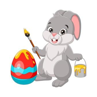 Coniglietto di pasqua del fumetto che dipinge un uovo