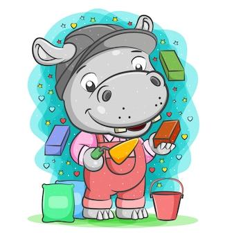 Il fumetto dell'ippopotamo grigio costruttore tiene il mattone con un cucchiaio di cemento