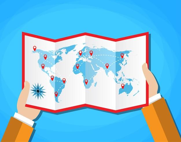 Le mani dei cartoni animati tengono la mappa cartacea piegata del mondo