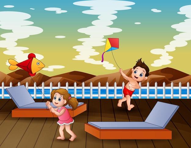 Bambini felici del fumetto che giocano aquilone sul molo