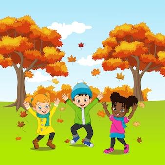 Bambini felici del fumetto che giocano nella priorità bassa di autunno
