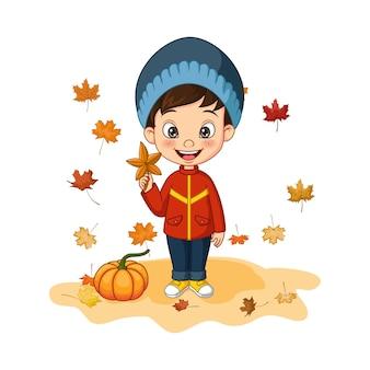 Ragazzino cartone animato in abiti autunnali e foglie che cadono