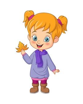 Bambina cartone animato in abiti autunnali che tiene foglia d'acero