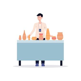 Uomo del fumetto alla mostra della ceramica in piedi dietro il tavolo che vende vasi e pentole di argilla ceramica. venditore maschio con stoviglie fatte a mano - illustrazione.