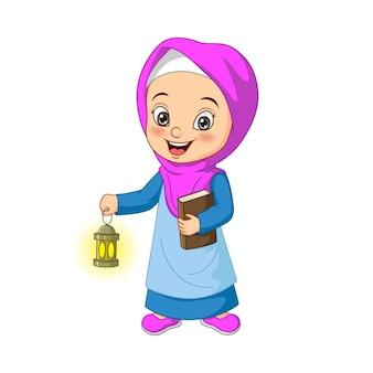 Ragazza musulmana del fumetto che tiene il libro del corano con la lanterna di ramadan