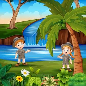 Cartone animato il ragazzo e la ragazza di safari in riva al fiume