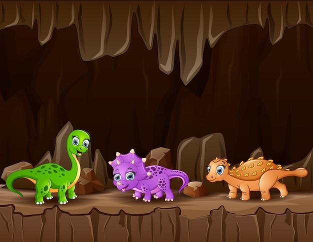 Cartone animato tre di dinosauri nella grotta oscura