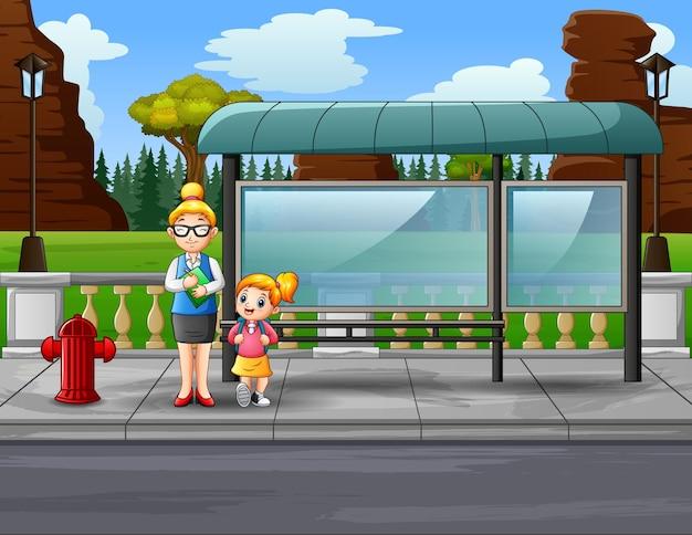 Cartoon una donna insegnante e il suo studente alla fermata dell'autobus Vettore Premium