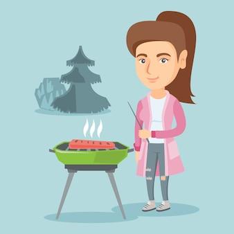 Donna caucasica che cucina bistecca sul barbecue.