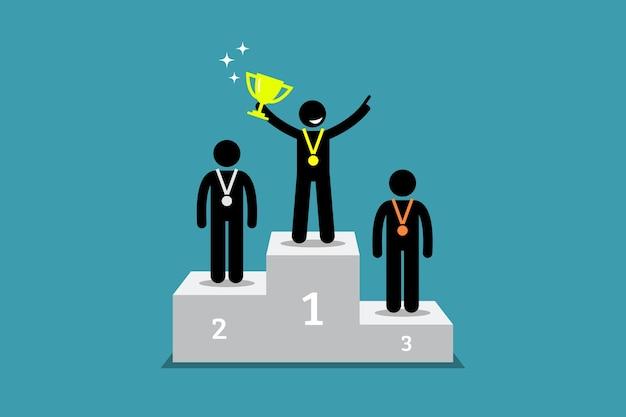 Campione in piedi su un podio con primo e secondo classificato.