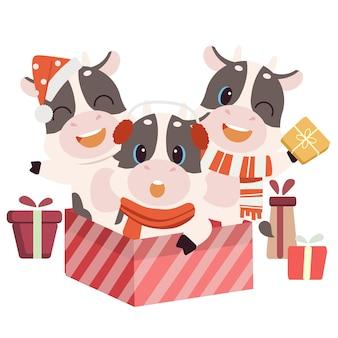 Il personaggio della mucca carina seduta nella confezione regalo di natale