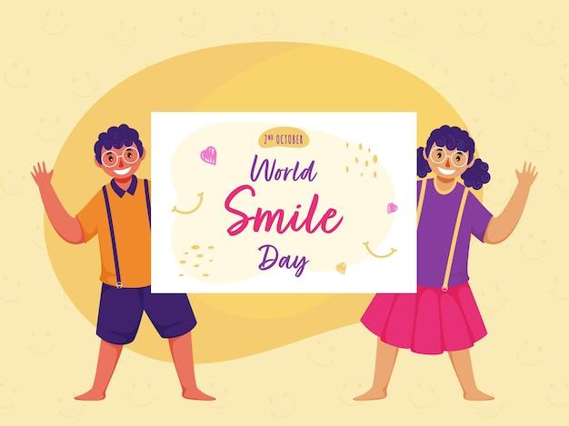 Ragazzo allegro e ragazza che tengono una carta del messaggio della giornata mondiale del sorriso sul fondo giallo del modello di faccina sorridente.