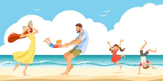La famiglia allegra che si riposa su una spiaggia sabbiosa in riva al mare