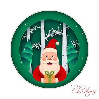 Carattere allegro del babbo natale che tiene un contenitore di regalo su carta verde e bianca ha tagliato il fondo della natura per la celebrazione di buon natale.