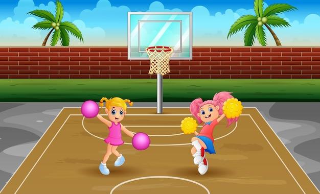 Ragazze pon pon che ballano sul campo da basket