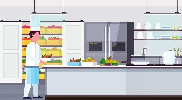 Piatto di trasporto del cuoco del cuoco unico con gli ingredienti del pasto degli ingredienti del pasto della verdura della frutta fresca che cucinano piano piano orizzontale interno della cucina commerciale moderna di concetto culinario e di concetto culinario