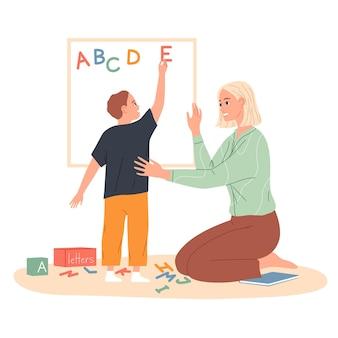 Il bambino fa un alfabeto inglese di lettere sulla lavagna