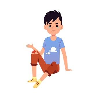 Bambino con ginocchio ferito seduto sul pavimento