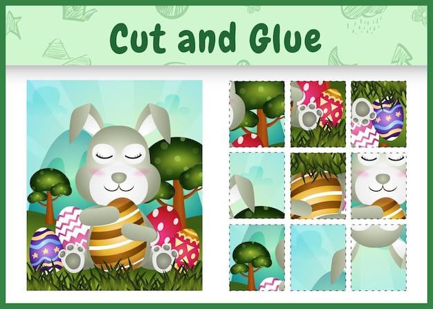 Gioco da tavolo per bambini taglia e incolla la pasqua a tema con un simpatico coniglio che abbraccia le uova