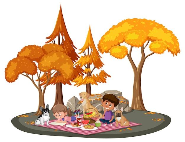 Bambini che fanno picnic nel parco con molti alberi autunnali