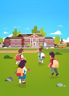 Gruppo di bambini con zaini in esecuzione per l'edificio scolastico educazione concetto mix gara vista posteriore alunni in cortile verde erba paesaggio sfondo piatto lunghezza verticale