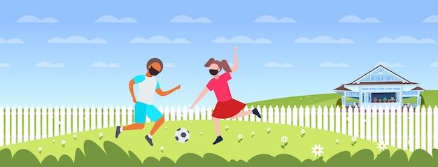 Bambini che giocano a calcio ragazzo ragazza in maschere per prevenire la quarantena della pandemia di coronavirus
