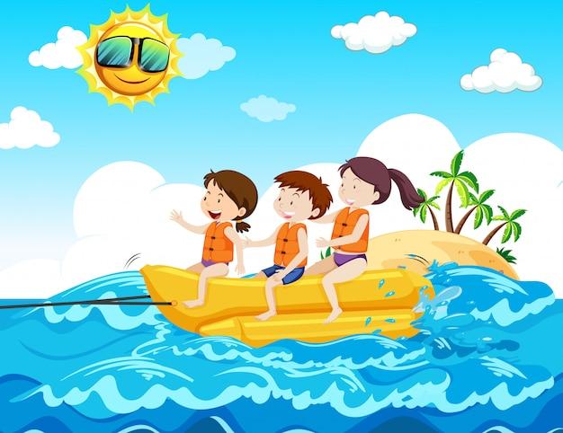Bambini che guidano la barca della banana alla spiaggia